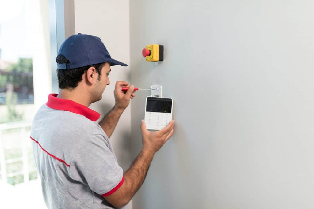Technician set up keypad of security alarm system