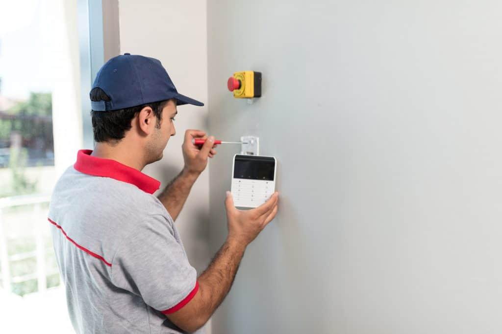 Technician set up keypad of security alarm system
